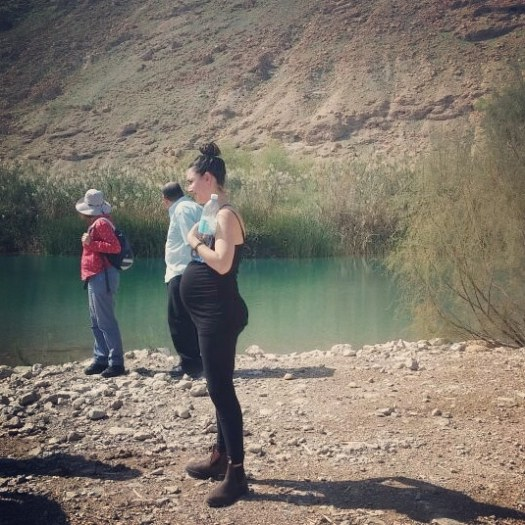 אישה בהריון עומדת ליד אגם- שמורת הטבע עיינות צוקים