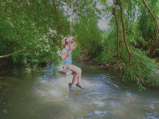 ילדה מתנדנדת במים. עין אביאל