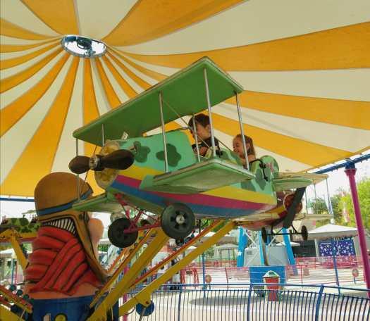 ילדים על מתקן מטוס מעופף. לונה פארק תל אביב