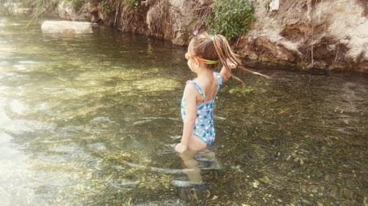 ילדה נהנית וזורקת אבן בתוך בריכת מים רדודים- הסחנה- גן לאומי גן השלושה