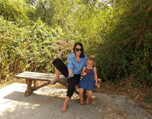אמא וילדה יושבות על ספסל בעמק החולה