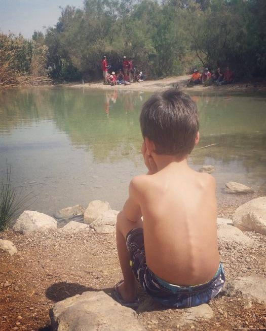 ילד יושב עם גבו למצלמה ומסתכל על מי האגם- עין פשחה
