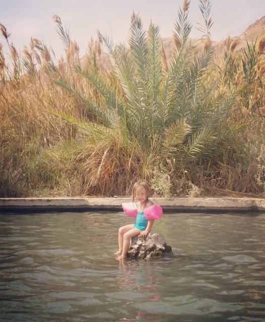 ילדה יושבת על סלע וצוחקת- שמורת הטבע עיינות צוקים