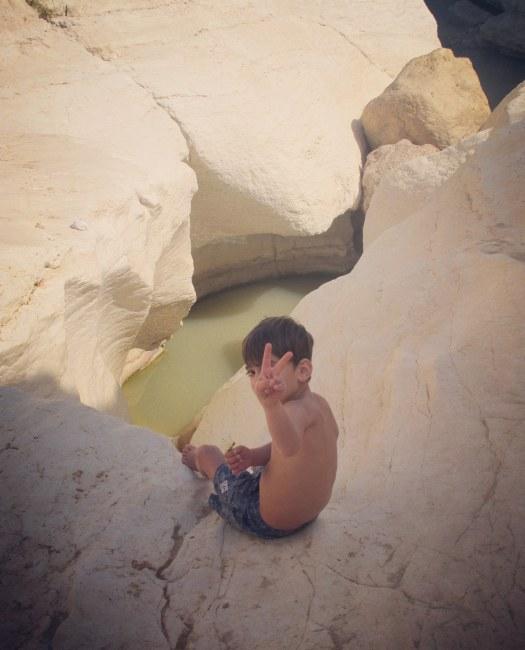 ילד יושב על הסלעים, שמורת עין ירקעם