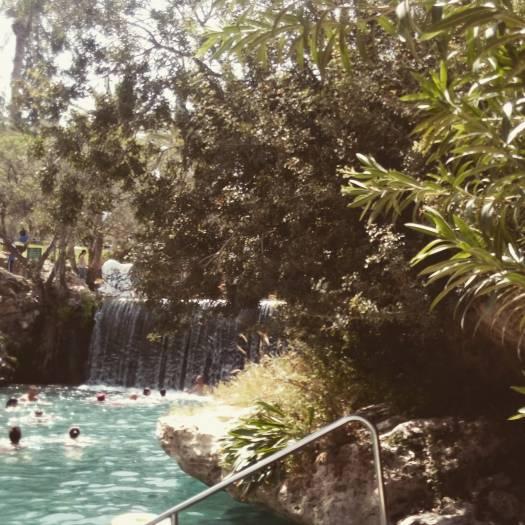 מפל מים ואנשים בתוך בריכת מים בסחנה- גן לאומי גן השלושה