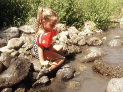 ילדה משחקת לצד הנחל