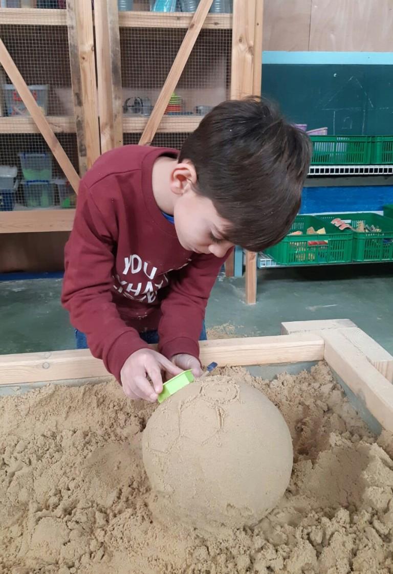 ילד מפסל כדורגל. מתחם החול יכול